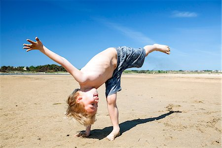 Blond boy on beach fooling around Stock Photo - Premium Royalty-Free, Code: 6115-08239255