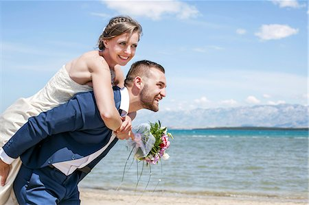 Bridegroom giving bride piggy back ride on beach Stock Photo - Premium Royalty-Free, Code: 6115-08239434