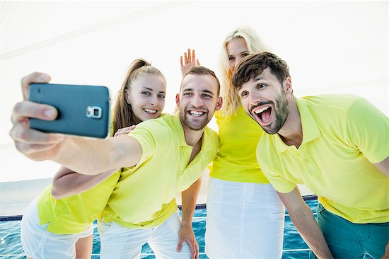Group of friends taking pictures on sailboat, Adriatic Sea Stock Photo - Premium Royalty-Free, Image code: 6115-08239772
