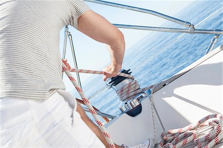 Man turning on cable winch on sailboat, Adriatic Sea Stock Photo - Premium Royalty-Free, Code: 6115-08239710