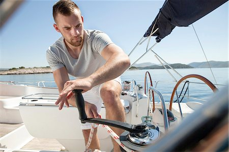 pulling - Man turning on cable winch on sailboat, Adriatic Sea Stock Photo - Premium Royalty-Free, Code: 6115-08239715