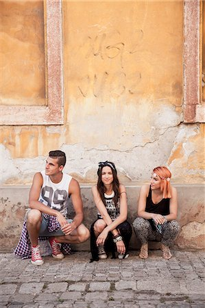 Young people in hippie style fashion crouching on sidewalk Stock Photo - Premium Royalty-Free, Code: 6115-08239902