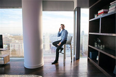 rich lifestyle - Businessman in apartment on the phone Stock Photo - Premium Royalty-Free, Code: 6115-08416148