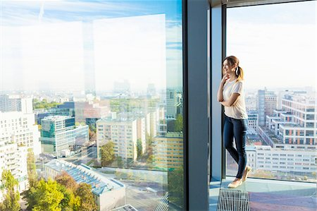 Woman in apartment looking through window Stock Photo - Premium Royalty-Free, Code: 6115-08416167