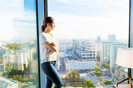 Woman in apartment looking through window Stock Photo - Premium Royalty-Free, Code: 6115-08416168