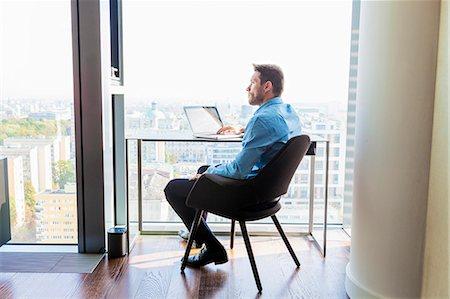 flat - Businessman in apartment using laptop computer Stock Photo - Premium Royalty-Free, Code: 6115-08416171