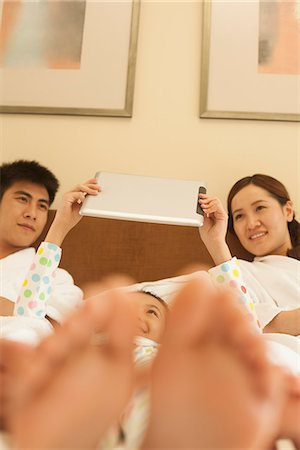 preteen feet - Family Using Tablet in Bed Stock Photo - Premium Royalty-Free, Code: 6116-06938711