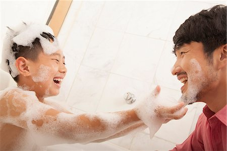 father son bath - Son in Bathtub puts Soap on His Father's Face Stock Photo - Premium Royalty-Free, Code: 6116-06938722