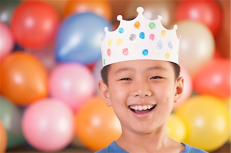 Birthday Boy Wearing a Crown in Front of Balloons Stock Photo - Premium Royalty-Free, Code: 6116-06938728