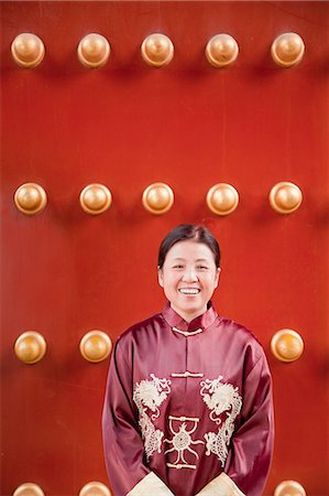 Mature woman in traditional clothes standing next to traditional Chinese door Stock Photo - Premium Royalty-Free, Code: 6116-06939046