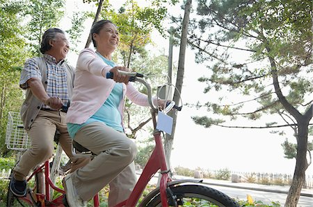 Older couple riding tandem bicycle, Beijing Stock Photo - Premium Royalty-Free, Code: 6116-06939001