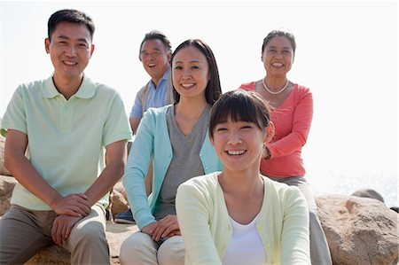 Portrait of smiling multigenerational family sitting on the rocks outdoors, China Stock Photo - Premium Royalty-Free, Code: 6116-06939008