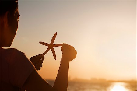 sea star - Teenage girl holding up starfish, sunset Stock Photo - Premium Royalty-Free, Code: 6116-06939025
