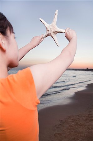 sea star - Teenage girl looking and holding up starfish Stock Photo - Premium Royalty-Free, Code: 6116-06939036