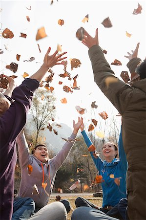 Group of young people throwing leaves Stock Photo - Premium Royalty-Free, Code: 6116-06939162