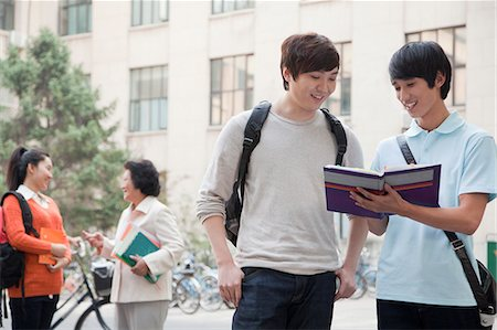 Students discussing and looking at the book, another student talking with professor on the background Stock Photo - Premium Royalty-Free, Code: 6116-06939103