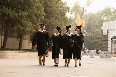 Young Graduates Walking Across Campus Stock Photo - Premium Royalty-Free, Code: 6116-06939206