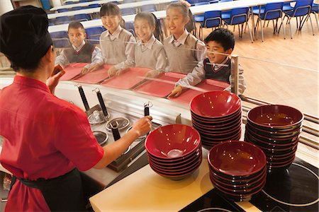 School cafeteria worker serves noodles to students Stock Photo - Premium Royalty-Free, Code: 6116-06939451