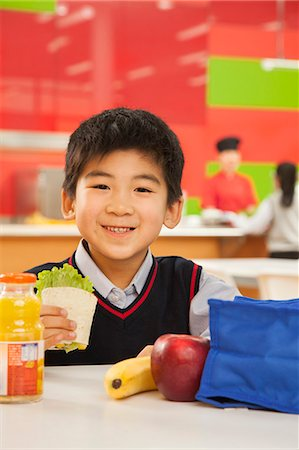 School boy portrait eating lunch in school cafeteria Stock Photo - Premium Royalty-Free, Code: 6116-06939458