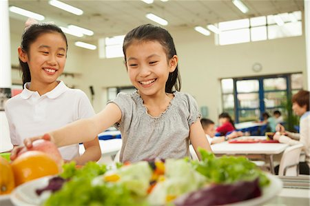 Students reaching for healthy food in school cafeteria Stock Photo - Premium Royalty-Free, Code: 6116-06939469