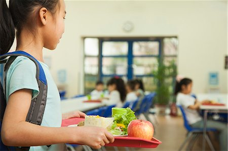 School girl holding food tray in school cafeteria Stock Photo - Premium Royalty-Free, Code: 6116-06939474