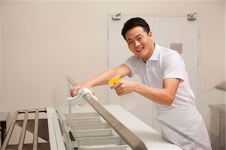 Cafeteria worker cleaning food serving area Stock Photo - Premium Royalty-Free, Code: 6116-06939482