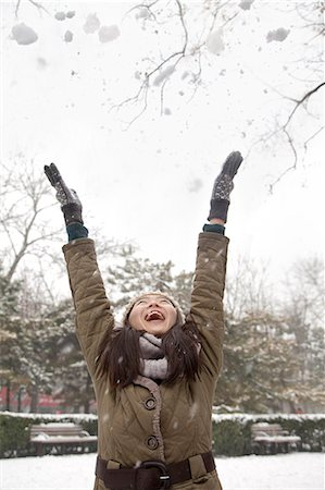 Young woman throwing snow into air in park Stock Photo - Premium Royalty-Free, Code: 6116-06939552