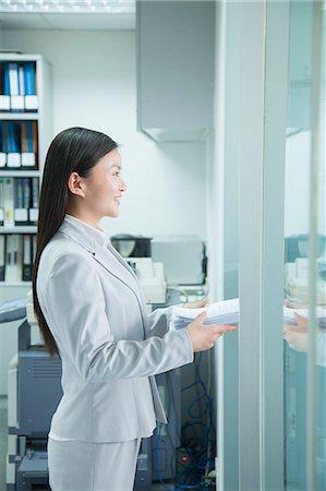 Businesswoman Handing Paper Through Doorway Stock Photo - Premium Royalty-Free, Code: 6116-06939571