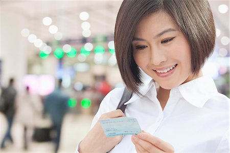 descriptive - Young Woman Looking at a Train Ticket Stock Photo - Premium Royalty-Free, Code: 6116-07084848