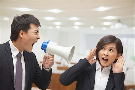 Businessman Talking into Megaphone by Businesswoman's Ear Stock Photo - Premium Royalty-Free, Code: 6116-07084858