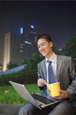 Young businessman working outdoors and eating Stock Photo - Premium Royalty-Free, Code: 6116-07085669