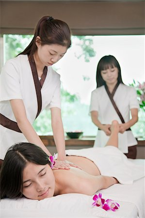 Two Masseuses Massaging One Woman Stock Photo - Premium Royalty-Free, Code: 6116-07085765