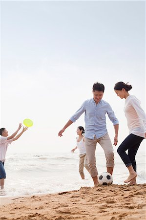 Four young people playing soccer and Frisbee on the beach, China Stock Photo - Premium Royalty-Free, Code: 6116-07085909