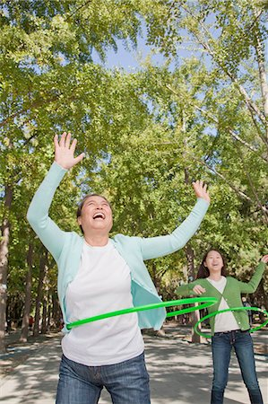 Granddaughter with grandmother playing with plastic hoop in the park Stock Photo - Premium Royalty-Free, Code: 6116-07085939