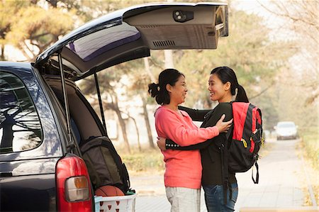 student (female) - Mother and daughter embracing behind car on college campus Stock Photo - Premium Royalty-Free, Code: 6116-07086146