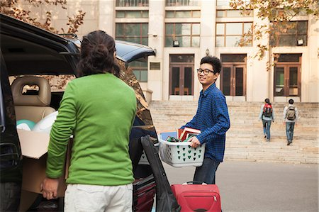 Young man moving into dormitory on college campus Stock Photo - Premium Royalty-Free, Code: 6116-07086152
