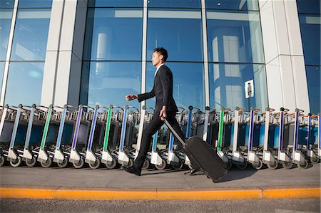 person walking on parking lot - Traveler walking fast next to row of luggage carts at airport Stock Photo - Premium Royalty-Free, Code: 6116-07086481