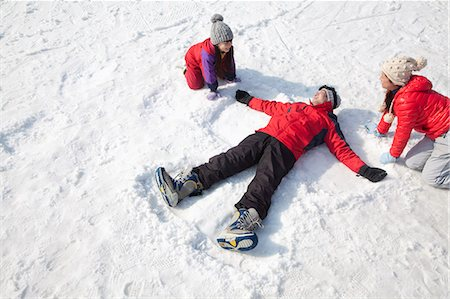 sports and snowboarding - Family Playing in the Snow, Father Making Snow Angel Stock Photo - Premium Royalty-Free, Code: 6116-07086620
