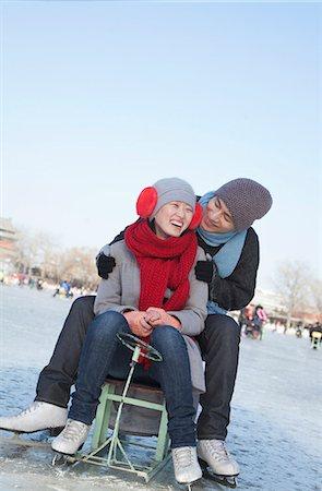 Young Couple Ice Skating, Sitting on Ice Sled Stock Photo - Premium Royalty-Free, Code: 6116-07235521