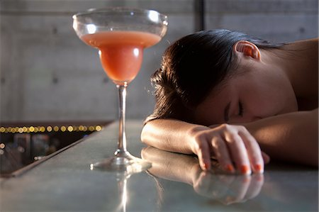 Young woman passed out on bar counter Stock Photo - Premium Royalty-Free, Code: 6116-07235672