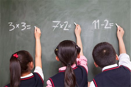 Three school children doing math equations on the blackboard Stock Photo - Premium Royalty-Free, Code: 6116-07235687