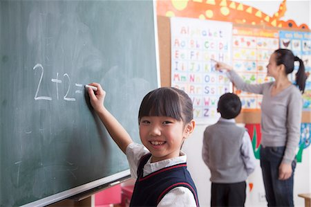 Schoolgirl doing math equation on the black board Stock Photo - Premium Royalty-Free, Code: 6116-07235686