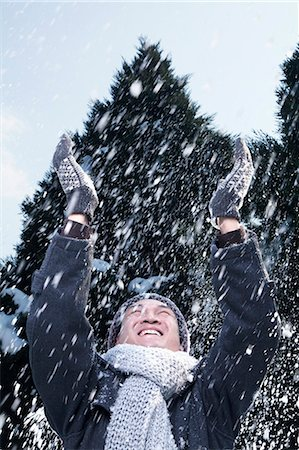 Man with arms raised feeling the snow Stock Photo - Premium Royalty-Free, Code: 6116-07235697