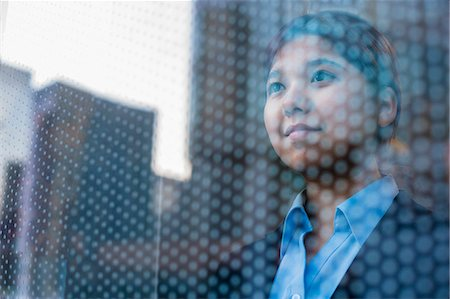 Businesswoman looking out through window, reflection of the city on the glass Stock Photo - Premium Royalty-Free, Code: 6116-07235783