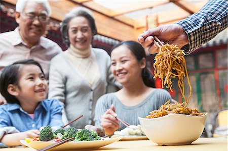 Father serving noodles with chopsticks at a family dinner Stock Photo - Premium Royalty-Free, Code: 6116-07235726