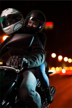 partnership - Young couple riding a motorcycle through the city streets at night in Beijing Stock Photo - Premium Royalty-Free, Code: 6116-07235916