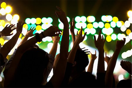 Audience watching a rock show, hands in the air, rear view, stage lights Stock Photo - Premium Royalty-Free, Code: 6116-07236047