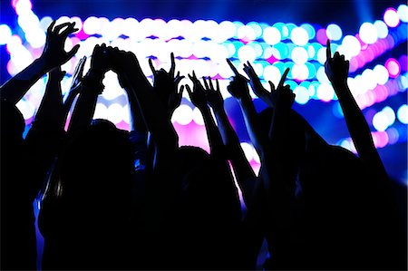Audience watching a rock show, hands in the air, rear view, stage lights Stock Photo - Premium Royalty-Free, Code: 6116-07236048