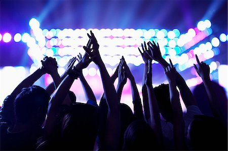 Audience watching a rock show, hands in the air, rear view, stage lights Stock Photo - Premium Royalty-Free, Code: 6116-07236049