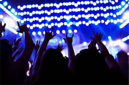 Audience watching a rock show, hands in the air, rear view, stage lights Stock Photo - Premium Royalty-Free, Code: 6116-07236050